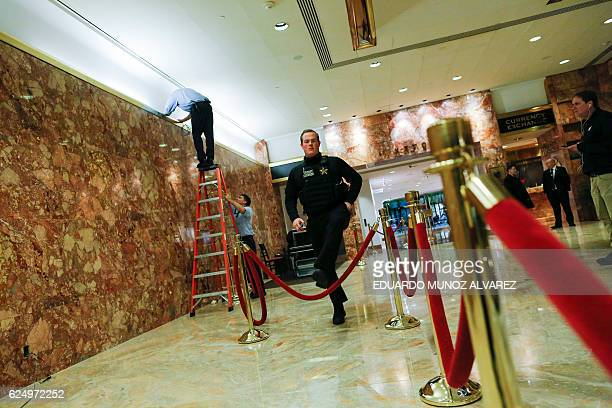 Workers try to fix a light as a secret service agent crosses protective ropes at Trump Tower during a day of meetings scheduled for US Presidentelect...