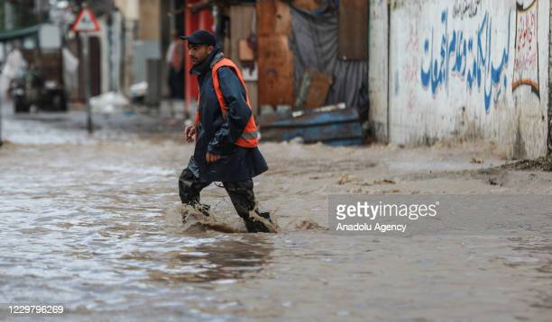 Workers try to open manholes on a flooded street caused by rainfall in Gaza City Gaza on November 26 2020