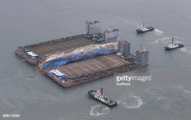 Workers try to raise the sunken Sewol ferry center between two barges during the salvage operation in waters off Jindo South Korea The 6800ton South...