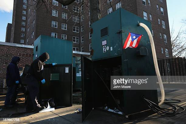 Workers try to repair a flooddamaged motor to run a trash compactor outside public housing projects in the Red Hook neighborhood of Brooklyn on...