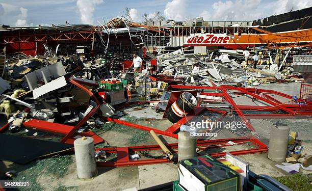 Workers try to salvage inventory at an Auto Zone car parts business that was totally destroyed in Port Charlotte Florida on Saturday August 14 2004...