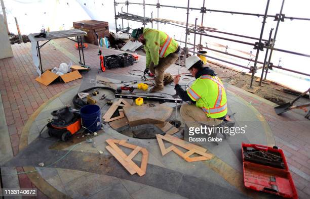 Workers under a tarp on the sidewalk of Boylston Street near the Boston Marathon finish line work on the base of a granite monument that will be...