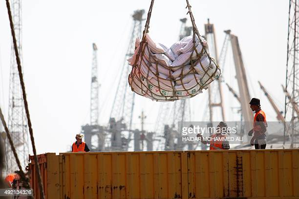Workers unload a cargo ship on October 10 2015 at the Iraqi port of Umm Qasr near the southern city of Basra AFP PHOTO / HAIDAR MOHAMMED ALI