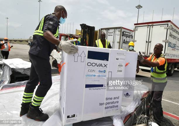 Workers unload a shipment of AstraZeneca Covid-19 vaccine bearing Covax stickers from a plane at Felix Houphouet Boigny airport of Abidjan on...