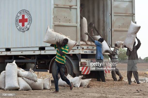 Workers unload a truck in Abathok village during an International Committee of the Red Cross distribution of seeds agricultural tools and food...