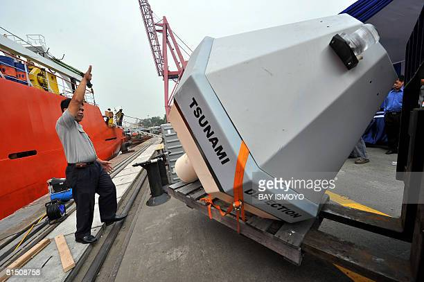 Workers unload a Tsunami Buoy a device to detect early tsunami warnings donated by the US National Oceanographic and Atmospheric Administration in...