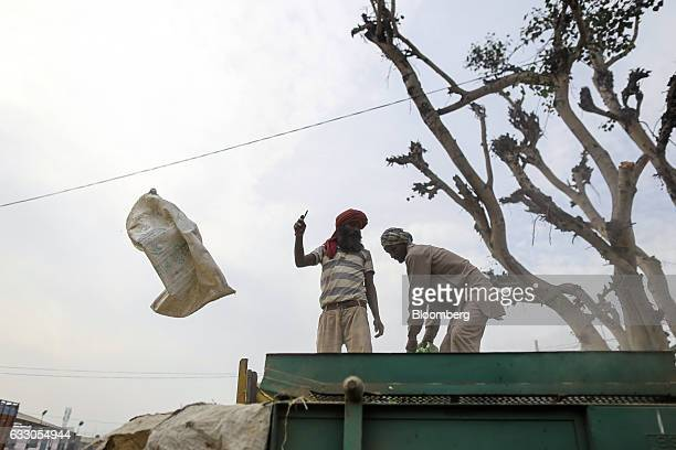 Workers unload bags of grain on to the back of a truck at an Agricultural Produce Market Committee wholesale market in Jalandhar Punjab India on...