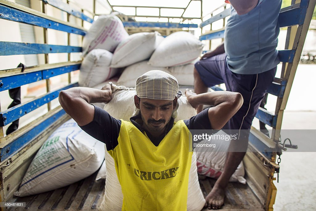 Workers unload bags of rice grain, to be dehusked and polished, from a truck at the KRK Modern Rice Mill in Kothapeta, Tamil Nadu, India, on Thursday, Nov. 14, 2013. Record onion prices and the soaring cost of rice and coriander are frustrating Reserve Bank of India Governor Raghuram Rajans battle to curb inflation while supporting growth in Asias third-largest economy. Photographer: Prashanth Vishwanathan/Bloomberg via Getty Images