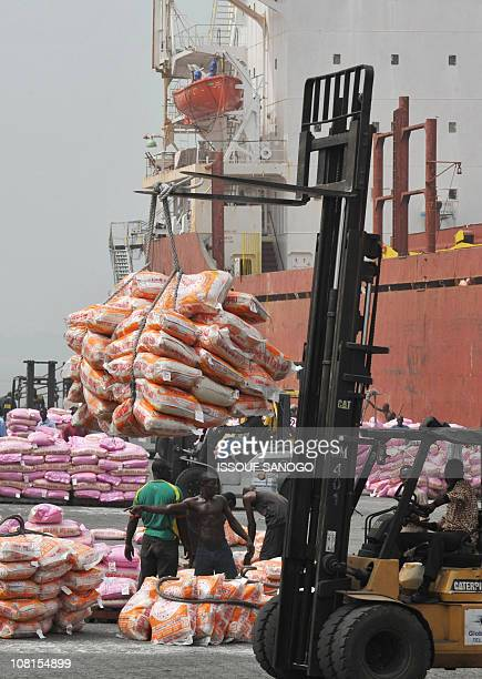 Workers unload bags of rice on January 19 2011 at the Port of Abidjan where 80% of Ivory Coast's exports transit EUregistered ships have been barred...