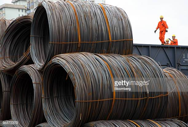 Workers unload bales of steel wire rod from a train carraige at a steel wholesale market in Shanghai China on Tuesday Nov 6 2007 China producer of...