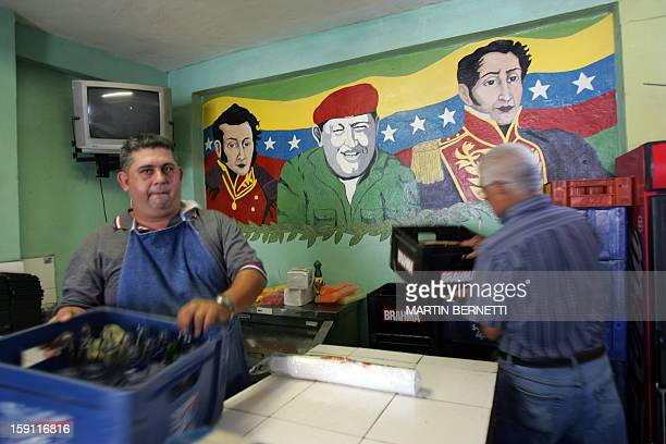 Workers unload beer crates in a restaurant in Caracas next to a mural painted with portraits of Venezuelan President Hugo Chavez and national...