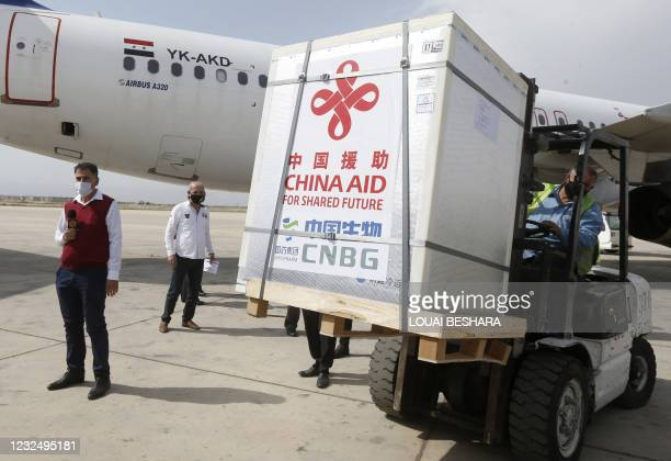 Workers unload boxes containing the Sinopharm Covid-19 vaccine, donated by China, at the Damascus International Airport on April 24 in the Syrian...