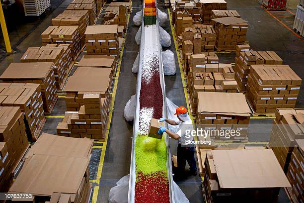 Workers unload boxes of specific jelly bean flavors to make an assorted variety at the Jelly Belly Candy Co. Manufacturing facility in Fairfield,...