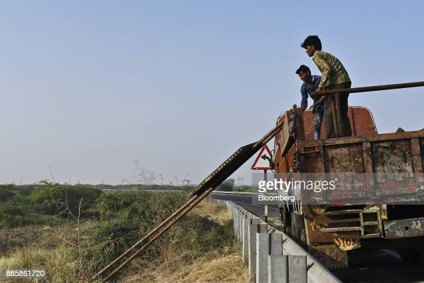 Workers unload building material from a truck on a project site for a 920squarekilometer industrial area located on the DelhiMumbai Industrial...