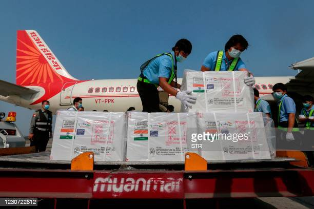 Workers unload cartons of a Covid-19 coronavirus vaccine being delivered from India to Myanmar, at Yangon International Airport in Yangon on January...