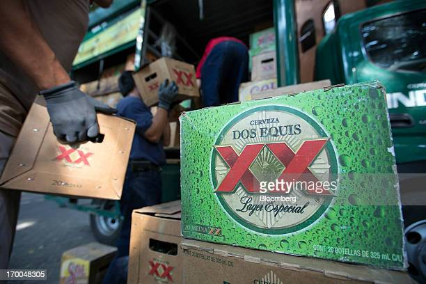 Workers unload cases of Grupo Modelo SAB's Dos Equis brand beer from a truck operated by CuauhtemocMoctezuma a subsidiary of Heineken NV while making...