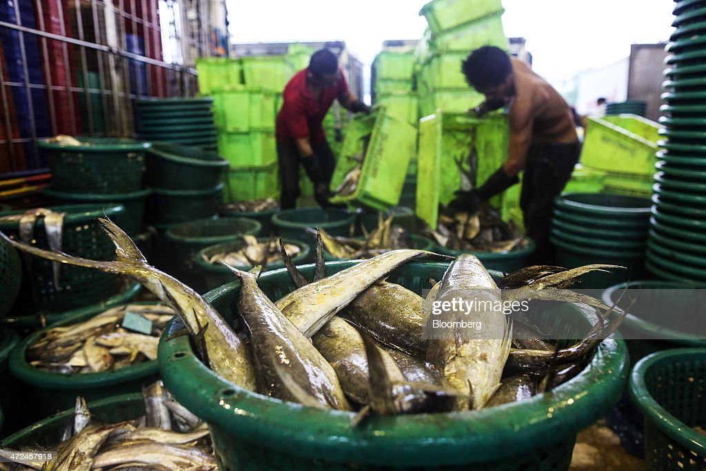 Workers unload fish into baskets for sale at the Talay Thai fish and