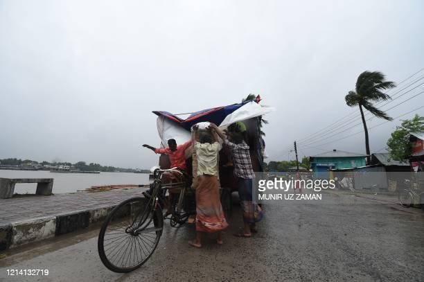 TOPSHOT Workers unload goods from a truck ahead of the expected landfall of cyclone Amphan in Khulna on May 20 2020 Several million people were...