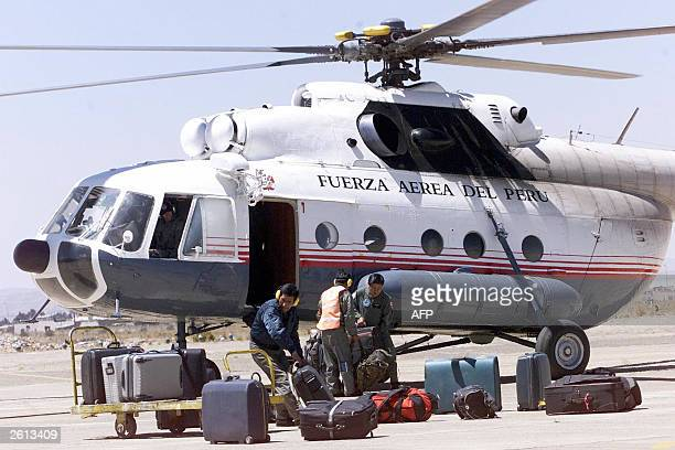 Workers unload luggage from a Peruvian military helicopter at El Alto military airport 18 October 2003 in El Alto 12 km from La Paz Many foreign...