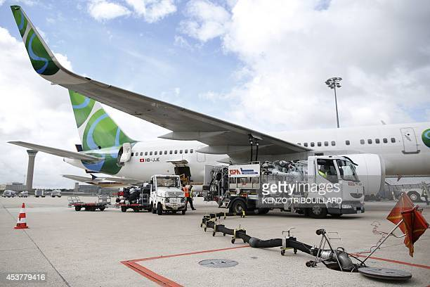 Workers unload luggages from an aircraft at the RoissyCharlesdeGaulle airport in RoissyenFrance on August 18 2014 AFP PHOTO / KENZO TRIBOUILLARD