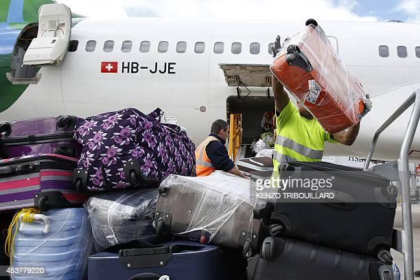 Workers unload luggages of an aircraft at the Roissy-Charles-de-Gaulle airport, in Roissy-en-France, on August 18, 2014. AFP PHOTO / KENZO...