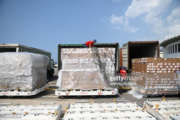 Workers unload medicines and disposable medical supplies from a Chinese Yangtze River Express Airlines Boeing 747 cargo plane after landing at Simon...