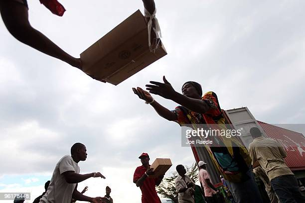 Workers unload packages of food during a German government food distribution program to help those displaced in the deadly January 12 earthquake on...