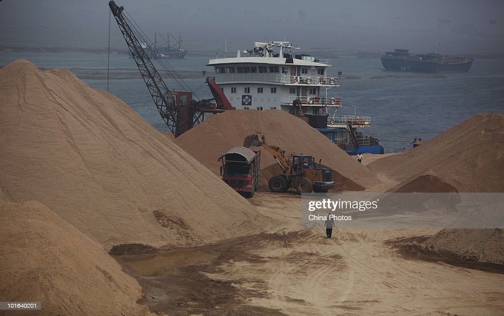 Workers unload sand from a ship at a land reclamation site of the Tanggu Coastal Economic Zone on June 5, 2010 in Tanggu of Tianjin Municipality, China. From 2002 to 2009, China reclaimed approximate 185,250 acres of land from sea, mainly for construction of industries, tourism and ports, according to the statistics released by the State Oceanic Administration (SOA).