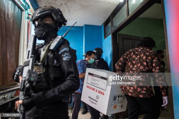 Workers unload Sinovac vaccines from a truck under police escort in Surabaya on January 4 as the distribution of as many as 3 million Sinovac doses...