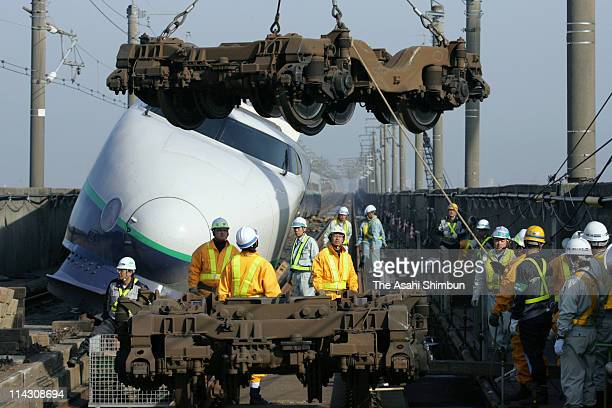 Workers unload the dolly to carry the derailed Joetsu Shinkansen carriage on November 10 2004 in Nagaoka Niigata Japan The quake later called...