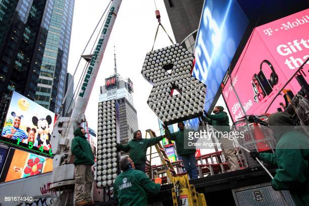 Workers unload the numerals 1 and 8 as they arrive in Times Square ahead of the New Year's Eve celebration arrive in Times Square December 13 2017 in...