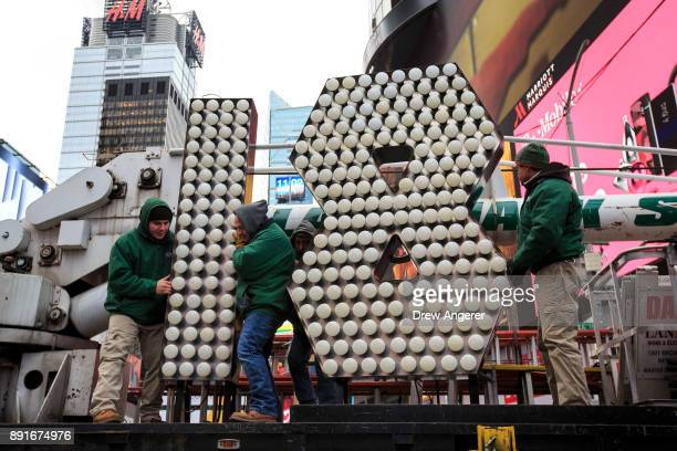Workers unload the numerals 1 and 8 as they arrive in Times Square ahead of the New Year's Eve celebration December 13 2017 in New York City The '18'...