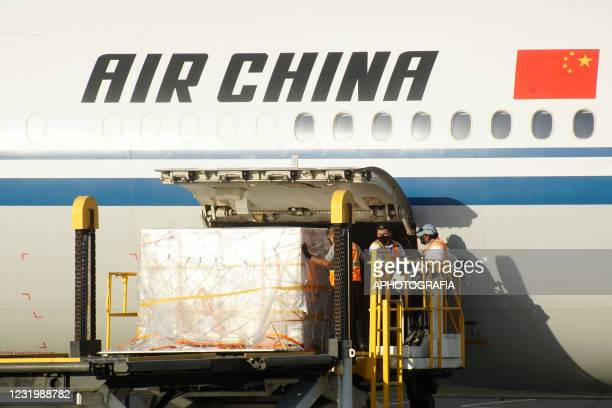 Workers unload vaccine doses from an Air China flight during the arrival of a new batch of Sinovac vaccines against Covid-19 at El Salvador...