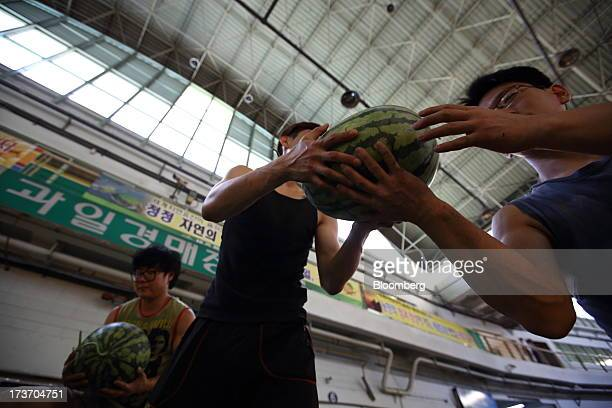 Workers unload watermelons from a truck at Noeun Agricultural and Marine Products Wholesale Market in Daejeon, South Korea, on Tuesday, July 16,...