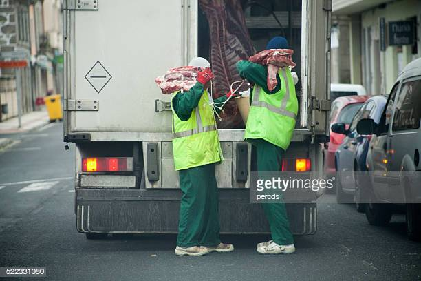 workers unloading meat delivery truck. - refrigerator truck stock pictures, royalty-free photos & images