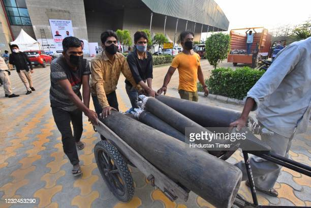 Workers unloading oxygen cylinders at the Commonwealth Games Village Covid-19 Care Centre, on April 21, 2021 in New Delhi, India.