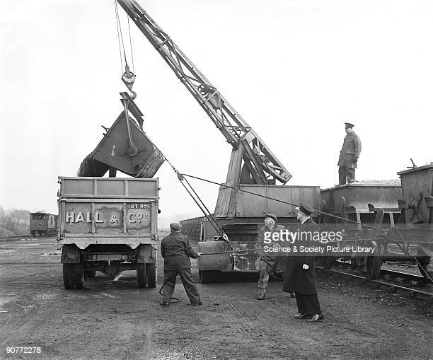 Workers unloading stone from a freight train to a lorry through the use of a crane Heavy loads were usually carried by rail at this time although...