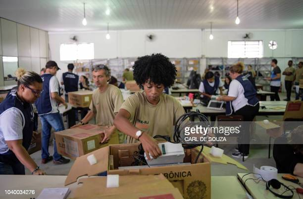 Workers unpack assemble and test electronic ballots that will be used in the first round elections on October 7 in Rio de Janeiro Brazil on September...