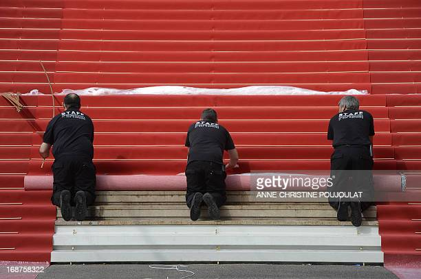 Workers unroll the red carpet at the entrance of the Palais des Festivals on the opening day of the 66th edition of the Cannes Film Festival on May...