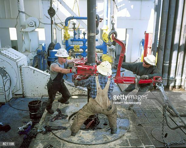 Workers unscrew two pieces of drilling pipe from one another March 19 2001 on a natural gas drilling rig in Lysite Wyoming Workers are pulling up...