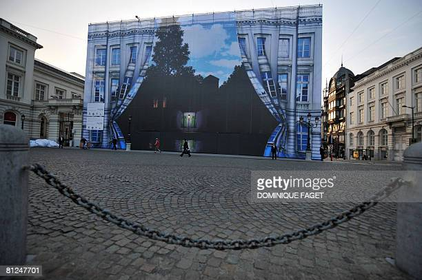 Workers unveil a giant tarpaulin bearing one of Belgian surrealist master Rene Magritte's most celebrated works Empire of Light in Brussels on May 27...
