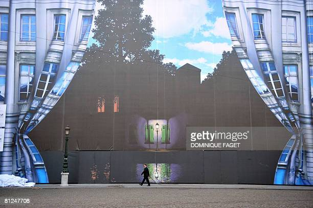 Workers unveil a giant tarpaulin bearing one of Belgian surrealist master Rene Magritte's most celebrated works 'Empire of Light' in Brussels on May...
