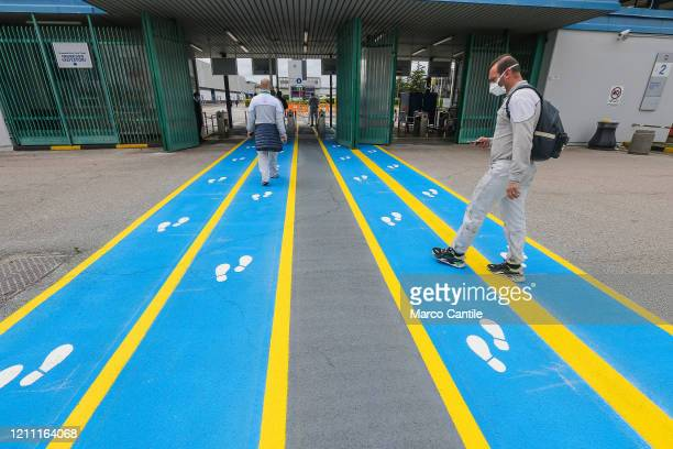Workers, upon arrival at the just reopened Gian Battista Vico Plant of the FCA automobile industry , walks along a track with footprint-shaped...