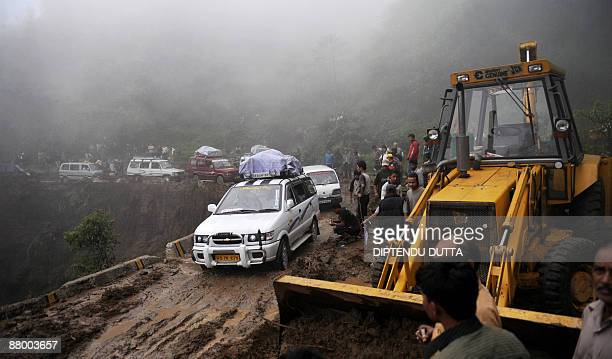 Workers use a bulldozer to clear the debris of a landslide on the National Highway 55 which connects the Darjeeling hills at Sonada some 70 kms from...