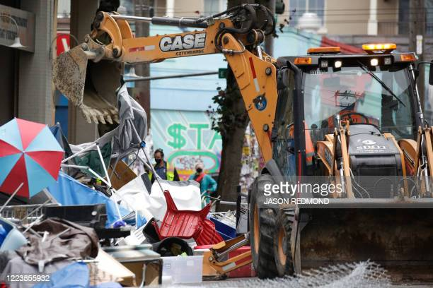 Workers use a bulldozer to remove remaining items from an encampment outside the Seattle Police Department's East Precinct after police cleared the...