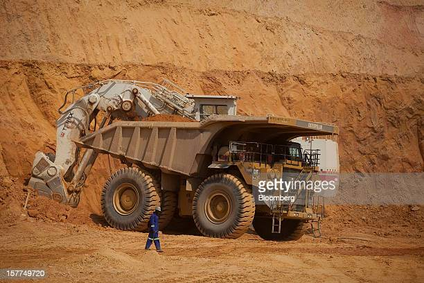 Workers use a Caterpillar Inc truck and a Terex Corp digger to excavate ore from the open pit at Katanga Mining Ltd's KOV copper and cobalt mine in...