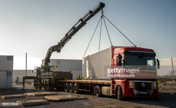 Workers use a crane to dismantle the Provisional Reception Center containers installed by the government to house up to 1500 migrants at the former...