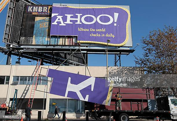 Workers use a crane to move a section of a Yahoo billboard onto a truck on December 21 2011 in San Francisco California Yahoo's iconic retrostyle...