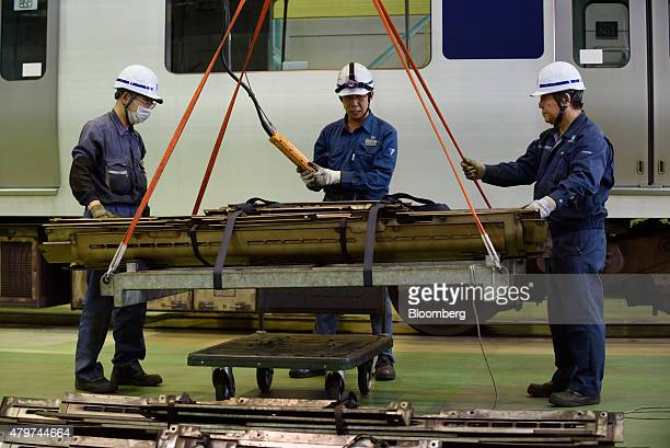 Workers use a crane to move an air conditioner component for a Tsukuba Express TX1000 series train at the Metropolitan Intercity Railway Co...