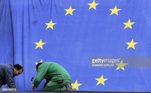 Workers use a hammer to fix a European Flag near the EU Headquarters in Brussels 21 March 2005 on the eve of the EU Spring Summit The European Union...